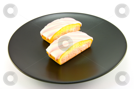 Cake Slices stock photo, Two strawberry sliced cakes with icing on the top and pink and yellow sponge on a black plate with a white background by Keith Wilson