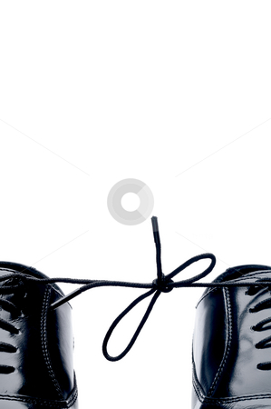Vertical close up of a pair of black leather business shoes with stock photo, Vertical close up of a pair of black leather business shoes with laces tied together by Vince Clements