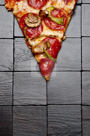 A slice of pizza on a black wooden background stock photo, A slice of pizza on a black wooden background by Vince Clements