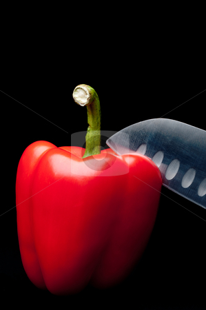 A vertical image of a red pepper being sliced on a dark backgrou stock photo, A vertical image of a red pepper being sliced on a dark background by Vince Clements