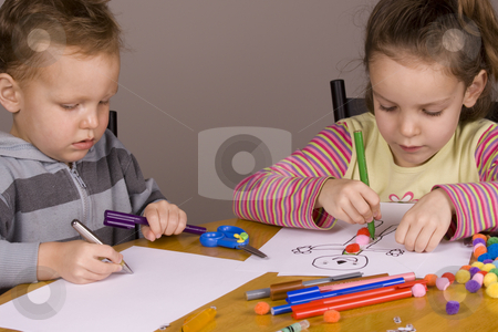 Girl and boy drawing stock photo, Girl and boy drawing a picture at the table by Jandrie Lombard