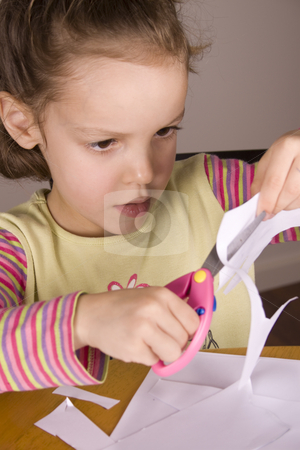 Girl using scissors stock photo, Little Girl cutting out her drawing with a pink pair of scissors by Jandrie Lombard