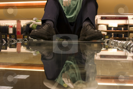 Mannequin sitting on the suits display stock photo, Mannequin sitting on the suits display rack with hands on the knees by Mehmet Dilsiz