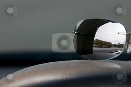 Sunglasses on the deck stock photo, School bus reflection on the sunglasses on the deck by Mehmet Dilsiz