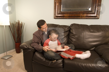 Father and Son Reading a Book on the Couch stock photo, Father is reading a book to his hyper son moving around by Mehmet Dilsiz
