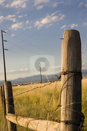Wooden Gate with Blue Skies in the Country stock photo, Wooden Fence with Electric Poles on the Background in Helena Montana by Mehmet Dilsiz