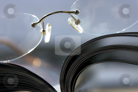 Close up on a pair of Glasses and the Magazine stock photo, Glasses and the Magazine - Extremen Close Up by Mehmet Dilsiz