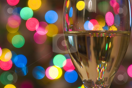 Celebrating the Holidays stock photo, Close up on a Wine Glass with the lights on the background by Mehmet Dilsiz