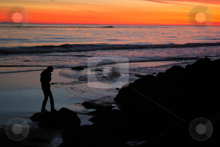 Silhouette at Sunset stock photo, A girl on the beach, talking on the phone in Southern California. by Kristine Keller