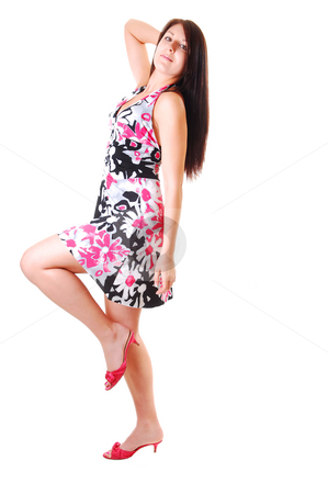 Woman dancing in dress. stock photo, Lovely young woman in high heels dancing in the studio with long brown hair and lifting up her leg, shooing her nice legs. by Horst Petzold