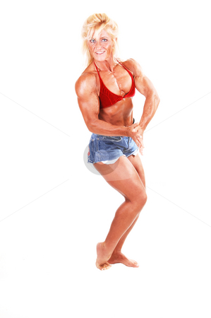 Bodybuilding woman. stock photo, A strong blond woman in jeans shorts and red bra standing bare foot in the studio and shooing her muscular body and bicep, over white. by Horst Petzold