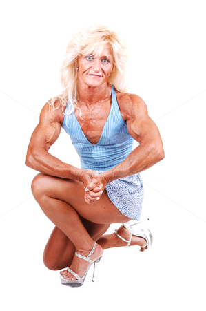Bodybuilding woman. stock photo, A blond muscular bodybuilding girl kneeling in the studio shooing her 