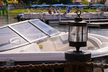 Pleasure Boats stock photo, Pleasure boats on the water with rope fence and lamp in the foreground by Keith Wilson