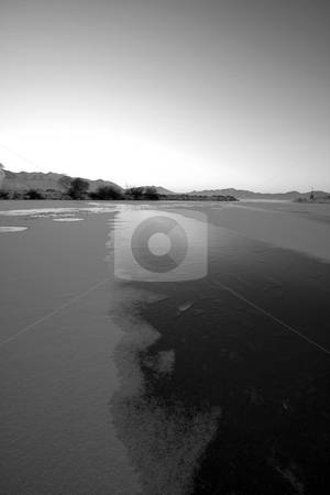 Sunrise over the Frozen Lake in Black and White stock photo, Sunrise over the Frozen Lake in Winter by Mehmet Dilsiz