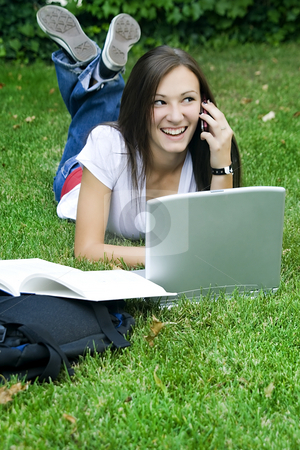Cute teen girl on the phone laying down on the grass studying stock photo, Cute teen girl laying down on the grass studying with her laptop by Mehmet Dilsiz