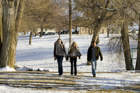People walking in the Park stock photo, People walking in the Park with Snow in Winter by Mehmet Dilsiz