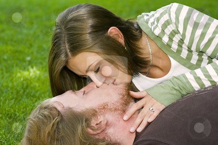 Young couple kissing in the Park stock photo, Young Married couple laying down on the grass kissing each other in a park by Mehmet Dilsiz