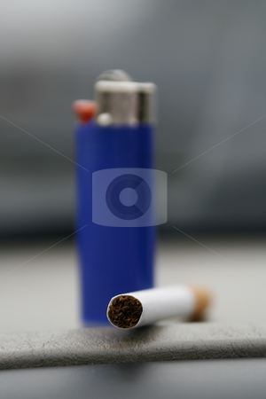 Blue Lighter and a Cigarette stock photo, Blue lighter standing with a cigarette on the deck by Mehmet Dilsiz