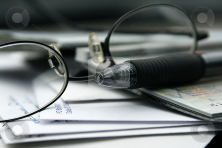 Paying the Bills with Checks stock photo, Close up on the Glasses and the Checkbook by Mehmet Dilsiz