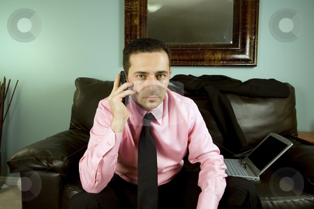 Businessman Talking on the Phone Sitting on the Couch stock photo, Businessman Talking on the Phone Sitting on the Couch Looking at the Camera by Mehmet Dilsiz