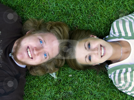 Young couple looking at the Camera stock photo, Young Married Couple laying down looking up at the camera by Mehmet Dilsiz