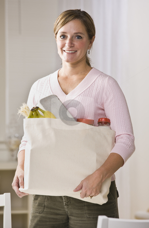 Woman Holding Groceries stock photo, A woman is standing in her kitchen and holding a bag of groceries.  She is smiling at the camera.  Vertically framed shot. by Jonathan Ross