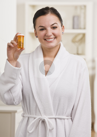 Woman Holding Bottle of Pills stock photo, A woman is standing in her bathroom and holding a bottle of pills.  She is smiling at the camera.  Vertically framed shot. by Jonathan Ross