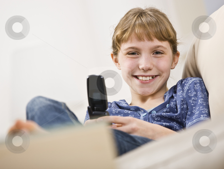 Girl Holding Cellphone stock photo, A young girl is holding a cellphone and smiling at the camera.  Horizontally framed shot. by Jonathan Ross