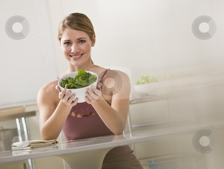 Woman Holding Bowl of Salad stock photo, A young woman is seated in the kitchen and is holding out a bowl of salad.  She is smiling at the camera.  Horizontally framed shot. by Jonathan Ross