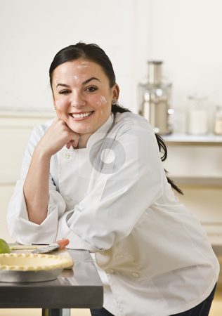 Chef Baking Pie stock photo, A woman is in a kitchen and baking a pie.  She is smiling at the camera and her face is covered in flour.  Vertically framed shot. by Jonathan Ross