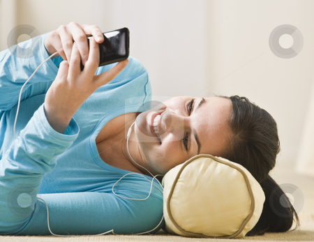 Woman With MP3 Player stock photo, A smiling young woman lies on the floor and looks at her mp3 player.  She is looking away from the camera.  Horizontally framed shot. by Jonathan Ross