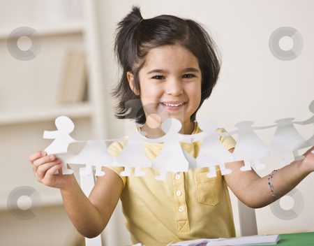 Girl Making Paper Dolls stock photo, A young girl is seated at a desk and is holding up paper dolls.  She is smiling at the camera.  Horizontally framed shot. by Jonathan Ross