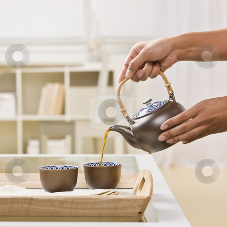 Woman Pouring Tea stock photo, A woman is pouring two cups of tea out of a tea kettle.  Square framed shot. by Jonathan Ross