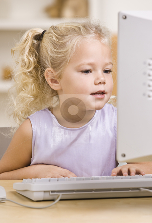Little Girl Using Computer stock photo, A beautiful little girl using a computer.  Vertically framed shot. by Jonathan Ross