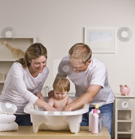 Happy Parents Bathing Baby stock photo, A happy couple bathing their baby.  Square framed shot. by Jonathan Ross