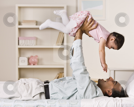 Father Holding Daughter stock photo, A father is holding his young daughter in the air above him.  They are smiling at each other.  Square framed shot. by Jonathan Ross