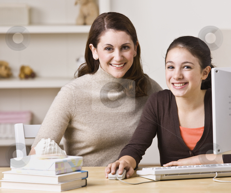 Mother and Daughter on Laptop stock photo, A mother and her daughter are working together on a laptop.  They are smiling at the camera.  Horizontally framed shot. by Jonathan Ross