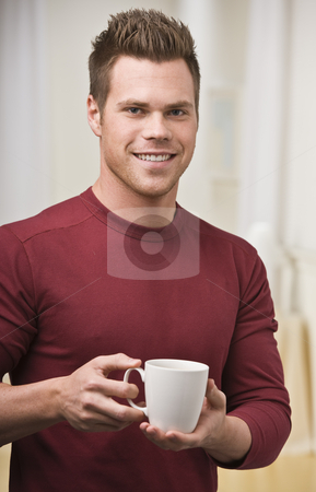 Man with Coffee Cup stock photo, A young man is holding a cup of coffee and smiling at the camera.  Vertically framed shot. by Jonathan Ross