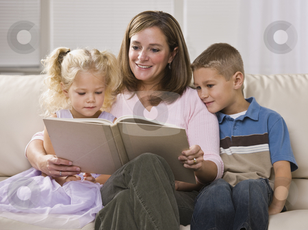 Happy Mother Reading to Children stock photo, A happy-looking mother reading to her son and daughter in their home.  Horizontally framed shot. by Jonathan Ross