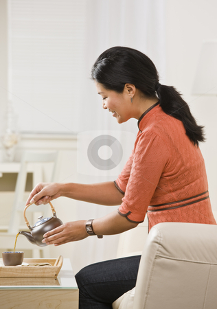 Woman Pouring Tea stock photo, A woman is seated on the living room sofa and pouring herself a cup of tea from the kettle.  She is looking away from the camera.  Vertically framed shot. by Jonathan Ross