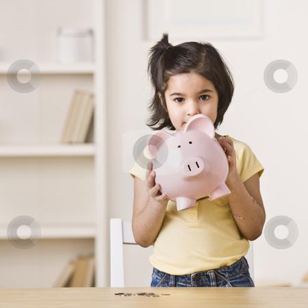 Little Girl Holding a Piggy Bank stock photo, A young girl holding a pink piggy bank.  Square framed shot. by Jonathan Ross