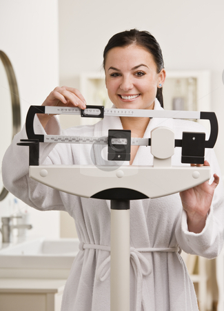 Woman Checking Weight stock photo, A young woman is checking her weight on a bathroom scale.  She is smiling at the camera.  Vertically framed shot. by Jonathan Ross