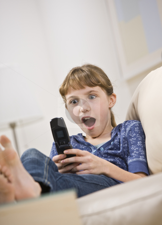 Excited Young Girl Looking at Cell Phone stock photo, A young girl sits on a couch, staring at her cell phone with a surprised expression.  Vertically framed shot. by Jonathan Ross