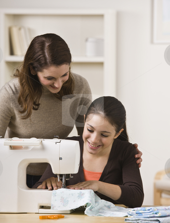 Mother Watching Daughter Use Sewing Machine stock photo, A beautiful teenage girl sewing on a sewing machine while her mother watches over her shoulder.  They are smiling.  Vertically framed shot. by Jonathan Ross