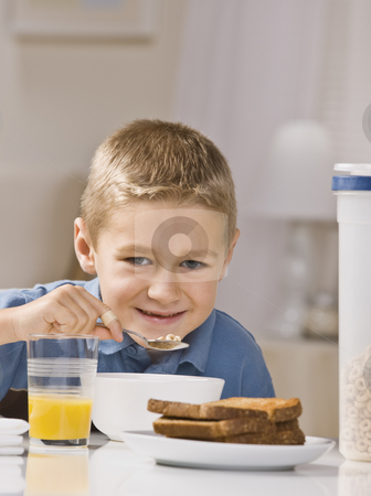 Boy Eating Breakfast stock photo, A young boy is eating breakfast and smiling at the camera.  Vertically framed shot. by Jonathan Ross