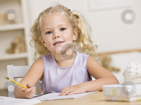Girl Coloring in Books stock photo, A young girl is sitting at a table and coloring in books.  She is looking at the camera.  Horizontally framed shot. by Jonathan Ross