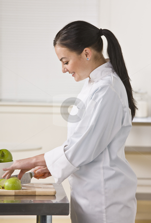 Woman Slicing Apples stock photo, A woman is standing in a kitchen and slicing apples.  She is looking away from the camera.  Vertically framed shot. by Jonathan Ross