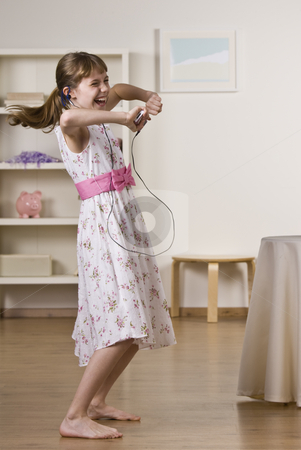 Little Girl Dancing to Music stock photo, A happy little girl dancing to music.  She is listening to headphones from an Mp3 player.  Vertically framed shot. by Jonathan Ross