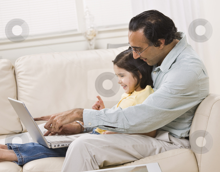 Indian Father and Daughter Look at Laptop Together stock photo, A smiling Indian father and daughter relax on the couch together and share a laptop.  Horizontally framed shot. by Jonathan Ross