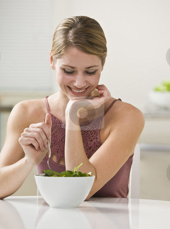 Woman Eating Salad stock photo, A young woman is eating salad and smiling.  Vertically framed shot. by Jonathan Ross